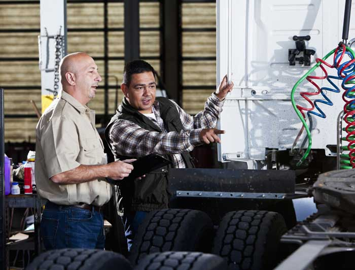 A CDL trainer and and trucking student looking over a commercial truck.