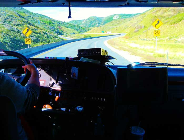 A commercial truck driver in the cab of his truck driving down a country road.