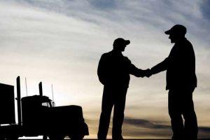 Verteran shaking hands with CDL trucking trainer.